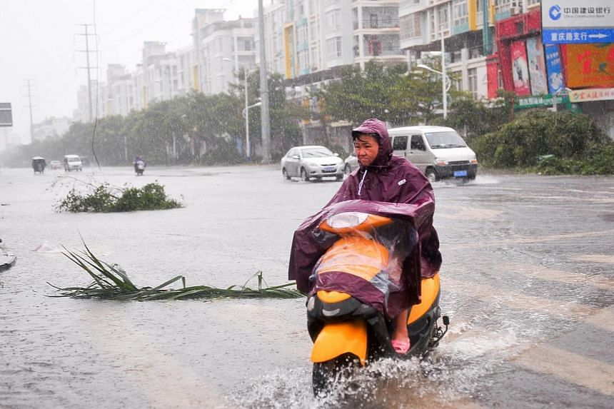 A woman rides a motor on a street as typhoon Rammasun brings torrential rains and strong wind to the area in Beihai, south China's Guangxi province on July 19, 2014. -- PHOTO: AFP