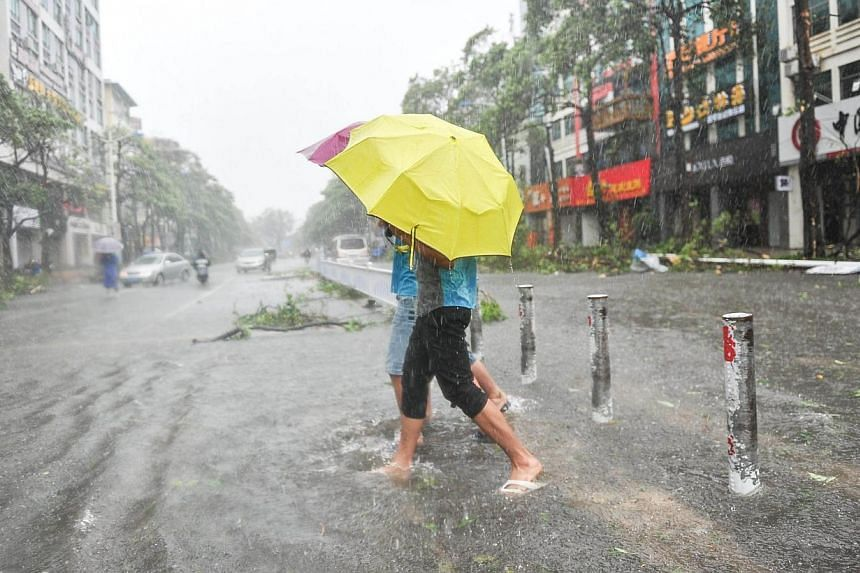 Residents walk on a street as typhoon Rammasun brings torrential rains and strong wind to the area in Beihai, south China's Guangxi province on July 19, 2014. -- PHOTO: AFP