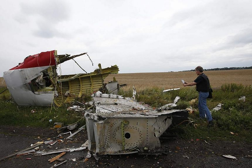 An Organisation for Security and Cooperation in Europe (OSCE) monitor takes a photograph at the crash site of Malaysia Airlines flight MH17, near the settlement of Grabovo in the Donetsk region on July 18, 2014.A Malaysian team, including two a