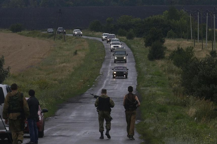 Pro-Russian separatists watch as Organisation for Security and Cooperation in Europe (OSCE) monitors arrive at the crash site of Malaysia Airlines flight MH17, near the settlement of Grabovo in the Donetsk region on July 18, 2014.Malaysian Tran