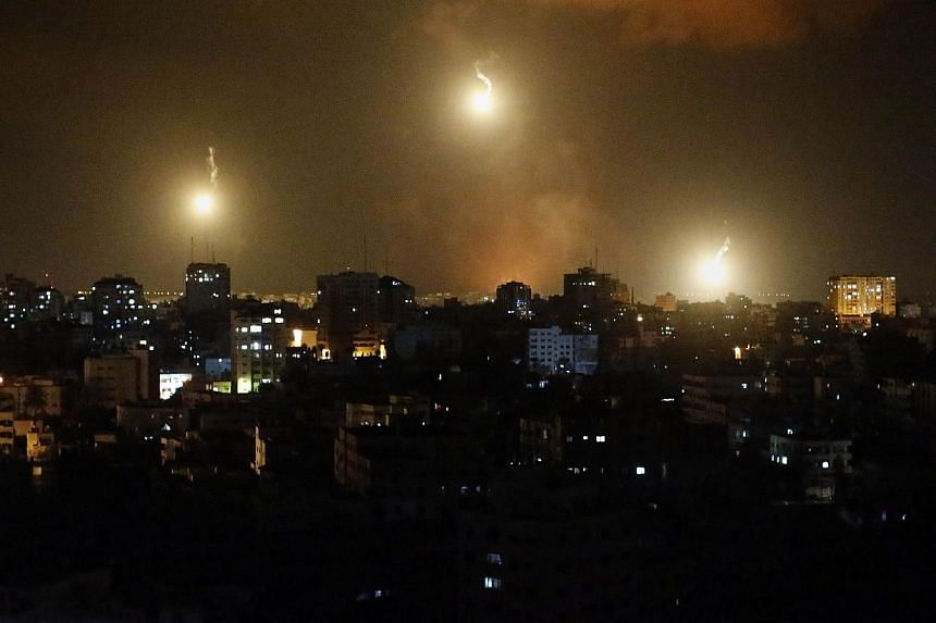 Three flares sent by Israeli army illuminate the eastern part of Gaza City, on July 18, 2014. Israel warned it could broaden a Gaza ground assault aimed at smashing Hamas' network of cross-border tunnels, as it intensified an operation that has so fa