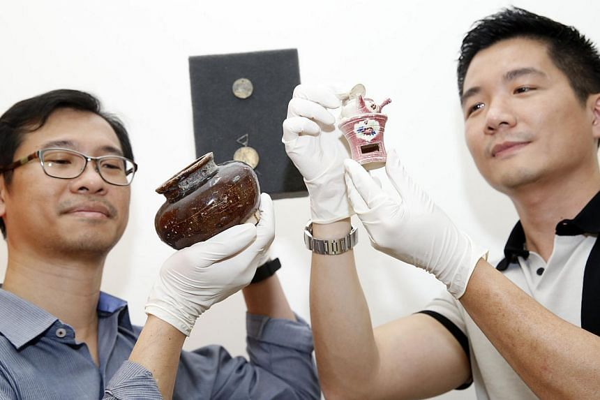 Iseas senior fellow Hui Yew-Foong (left) holding a ceramic pot and National Heritage Board group director for policy Alvin Tan with a miniature vessel. Behind them is the Total Abstinence medal.