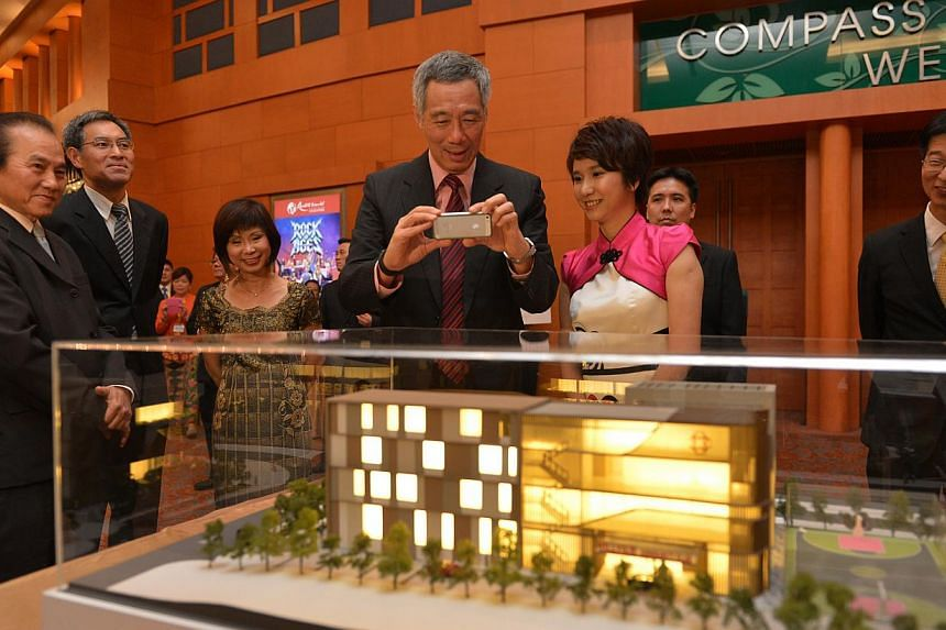 PM Lee (centre) takes a photo of the model of new Bukit Gombak Community Club as Ms Low Yen Ling, (second, right), Mayor of South West District, looks on. With them are (from left) Mr Joe Chan, PBM, Organising Chairman of Bukit Gombak Community Club