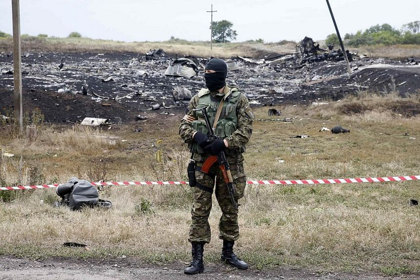 A pro-Russian separatist stands at the crash site of Malaysia Airlines Flight MH17, near the settlement of Grabovo in the Donetsk region July 19, 2014. -- PHOTO: REUTERS