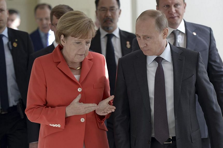 Russian President Vladimir Putin (right) and German Chancellor Angela Merkel walk during a meeting in Rio de Janeiro on July 13, 2014. -- PHOTO: REUTERS