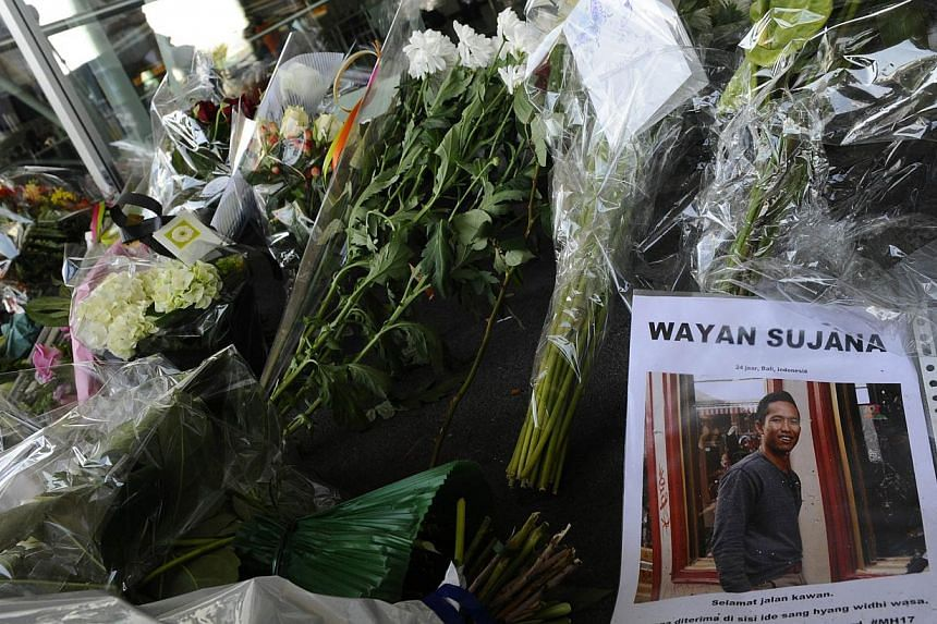 A picture taken on July 18, 2014 shows flowers and a picture of a man who was on board flight MH17, in front of the Schiphol airport, a day after the plane crashed in eastern Ukraine. United States President Barack Obama said the downing of the jetli