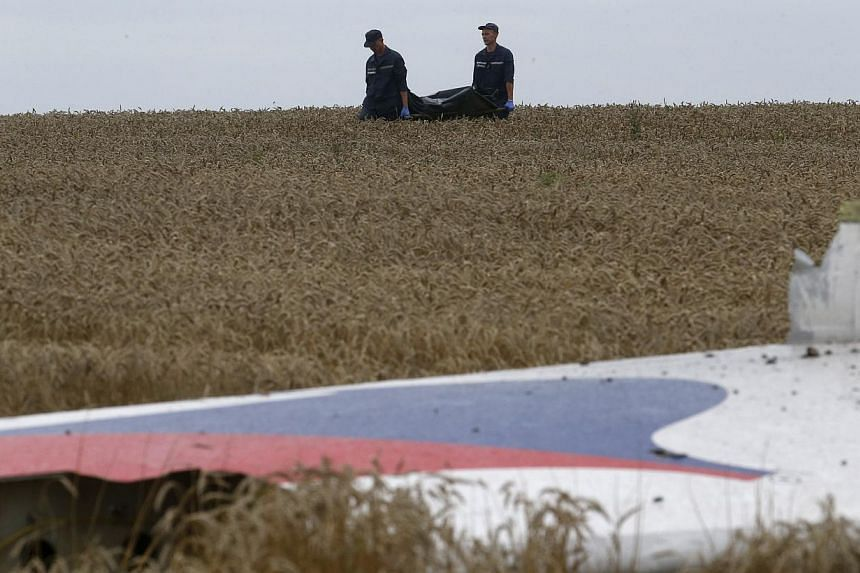 Members of the Ukrainian Emergency Ministry carry a body near the wreckage at the crash site of Malaysia Airlines Flight MH17, near the settlement of Grabovo in the Donetsk region ON July 19, 2014. -- PHOTO: REUTERS