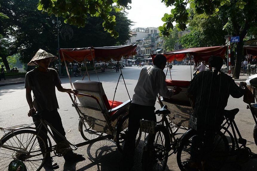 This picture taken on July 16, 014 shows cyclo drivers waiting for foreign tourists in Hanoi downtown. Relations between the communist neighbours plunged to their lowest point in decades when Beijing moved a deep-sea oil rig into disputed waters