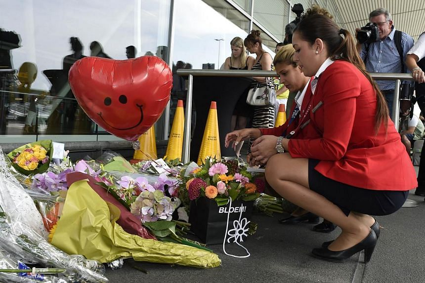 Delta Airlines flight attendants place flowers in front of Schiphol airport on July 19, 2014, two days after Malaysia Airlines flight MH17 carrying 298 people from Amsterdam to Kuala Lumpur crashed in eastern Ukraine. -- PHOTO: AFP