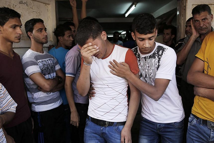 A relative of Palestinians, who medics said were killed overnight by Israeli shelling, grieve at their funeral in Khan Younis in the southern Gaza Strip on July 19, 2014.-- PHOTO: REUTERS