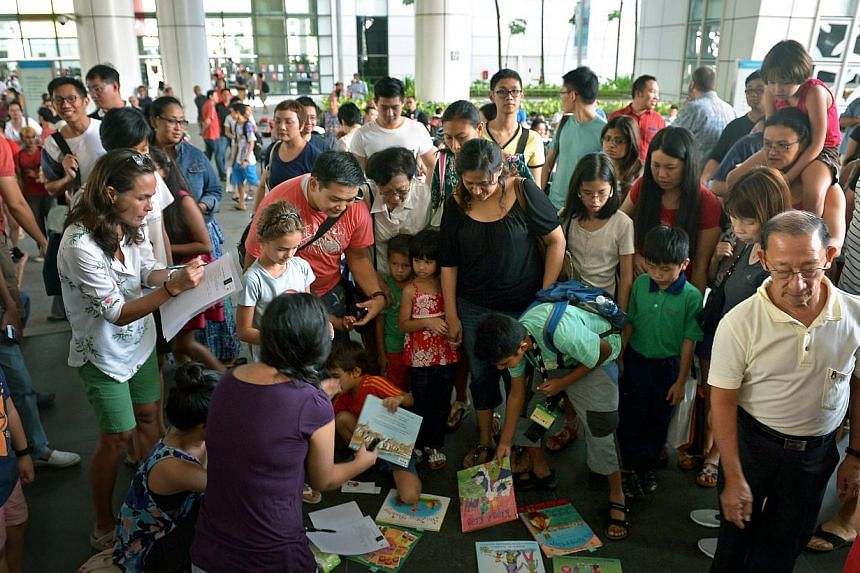 """Parents and children checking out the books at the makeshift """"library corner"""" set up at The Let's Read Together event at the National Library Building's atriumon 13 July 2014, held in response to the National Library Board's (NLB) dec"""