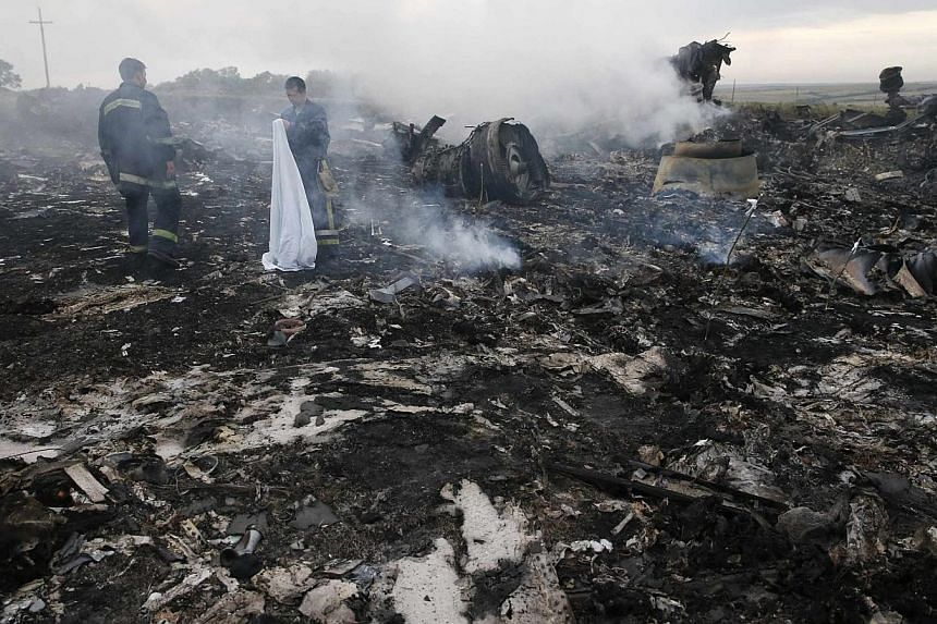 Emergencies Ministry members gather at the site of a Malaysia Airlines Boeing 777 plane crash near the settlement of Grabovo in the Donetsk region, July 17, 2014. Ukraine on Saturday accused Russia of helping insurgents destroy evidence at the c