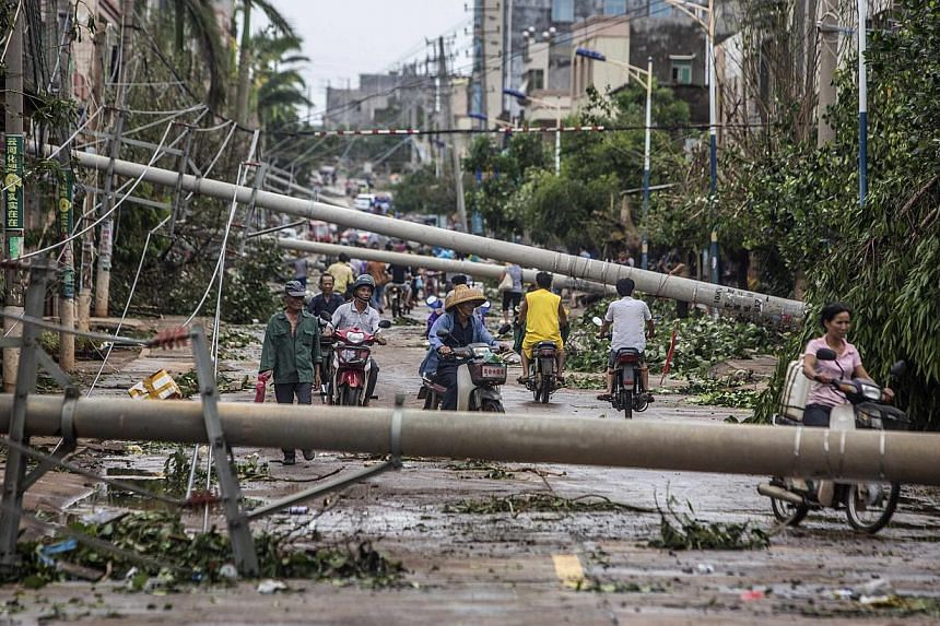 Residents travel on a street blocked by fallen electricity poles after Typhoon Rammasun hit Leizhou, Guangdong province on July 19, 2014.The death toll from the strongest storm to hit China in decades has reached 17, state media said on Sunday,