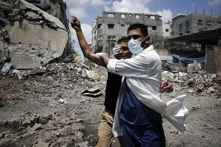 A medic helps a Palestinian in the Shejaia neighbourhood, which was heavily shelled by Israel during fighting, in Gaza City on Sunday, July 20, 2014.US Secretary of State John Kerry on Sunday blamed Hamas for the continuation of the conflict in