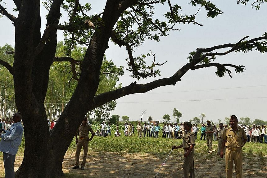 Indian police keep watch under the tree where the bodies of two gang-rape victims were found hanging in the village of Katra Shahadatgunj in Badaun in the Indian state of Uttar Pradesh,on May 31, 2014.India's monsoon rains on Sunday, July