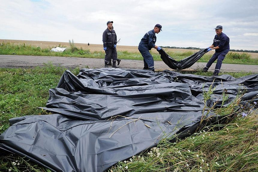 Ukrainian rescue workers collect bodies of victims at the site of the crash of a Malaysia Airlines plane carrying 298 people from Amsterdam to Kuala Lumpur in Grabove, in rebel-held east Ukraine. Scores of bodies that had been gathered at the ma