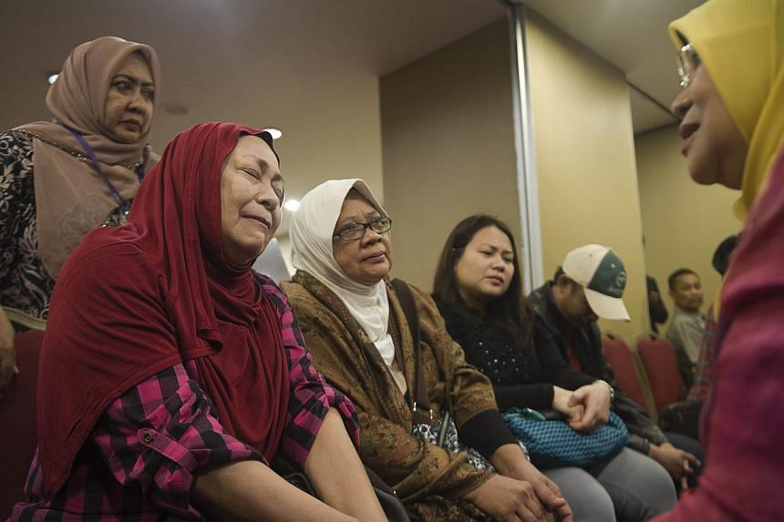 Relatives of a passenger who was on board Malaysia Airlines flight MH17 from Amsterdam to Kuala Lumpur meet with Malaysia's Woman, Family and Community development Minister Rohani Abdul Karim (right) at a hotel in Putrajaya on July 20, 2014. Fam