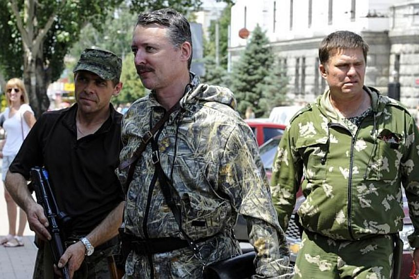 """Commander and self-proclaimed minister of Defence of so the called """"Donetsk People's Republic"""" Igor Girkin, aka Strelok (centre), walks with his bodyguards in the eastern Ukrainian city of Donetsk on July 11, 2014.Pro-Russian separatist leader"""