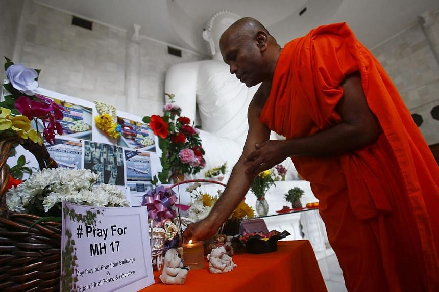 A monk performs a prayer during a special vigil for victims of the downed Malaysia Airlines Flight MH17, inside a Buddhist temple in Kuala Lumpur July 20, 2014. More than a hundred Buddhist devotees and members of the public turned up for a memorial