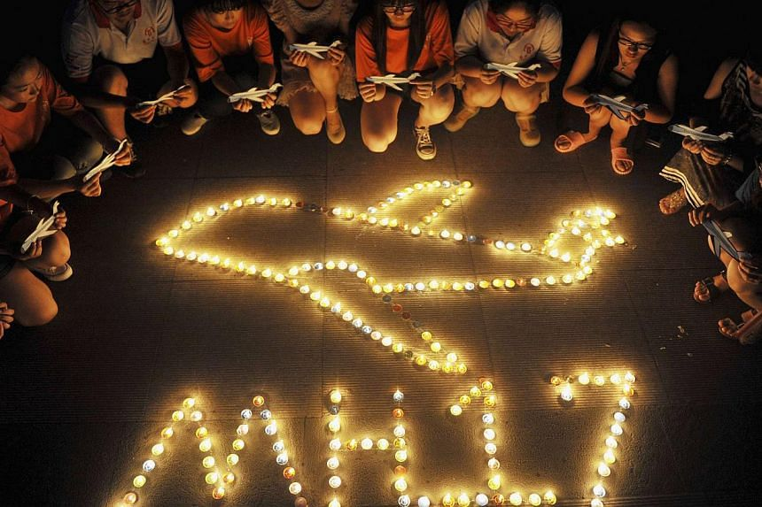 College students gather around candles forming the shape of an airplane, during a candlelight vigil for victims of the downed Malaysia Airlines Flight MH17, at a university in Yangzhou, Jiangsu province on July 19, 2014.Malaysia Airlines said o