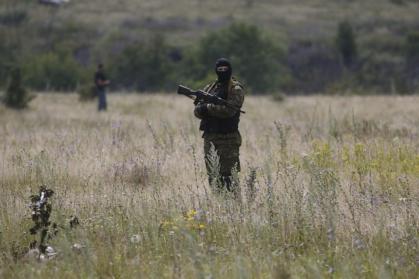 A pro-Russian separatist stands at the crash site of Malaysia Airlines Flight MH17, near the settlement of Grabovo in the Donetsk region on July 19, 2014.A spokesman for Ukraine's Security Council said on Sunday, July 20, 2014, that pro-Russian
