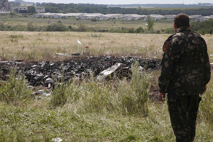 A pro-Russian separatist stands at the crash site of Malaysia Airlines Flight MH17, near the settlement of Grabovo in the Donetsk region on July 19, 2014.A top Ukrainian rebel leader said on Sunday, July 20, 2014 that the pro-Russian fighters w