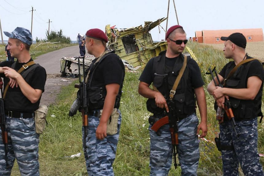 Armed pro-Russian separatists stand guard at a crash site of Malaysia Airlines Flight MH17, near the village of Hrabove, Donetsk region on Sunday, July 20, 2014.France, Britain and Germany warned Russia on Sunday it could face further EU sancti