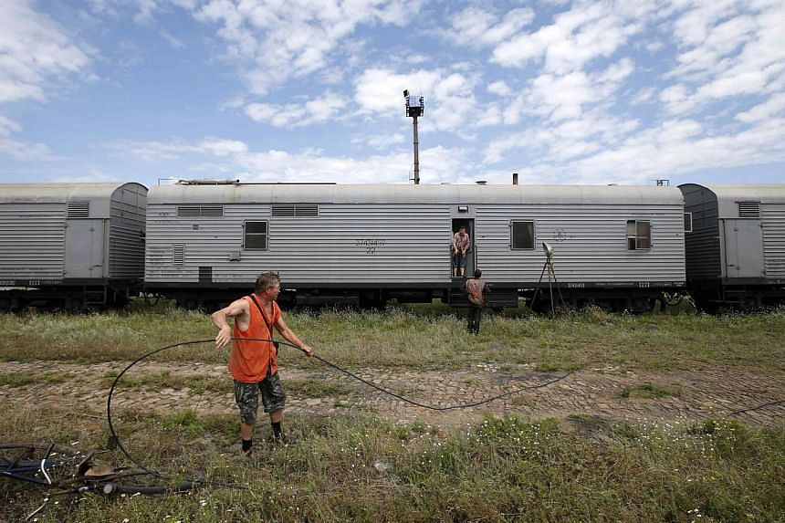 Railway employees are pictured as they work near refrigerator wagons, which according to employees and local residents contain bodies of passengers of the crashed Malaysia Airlines Boeing 777 plane, at a railway station in the town of Torez, Donetsk