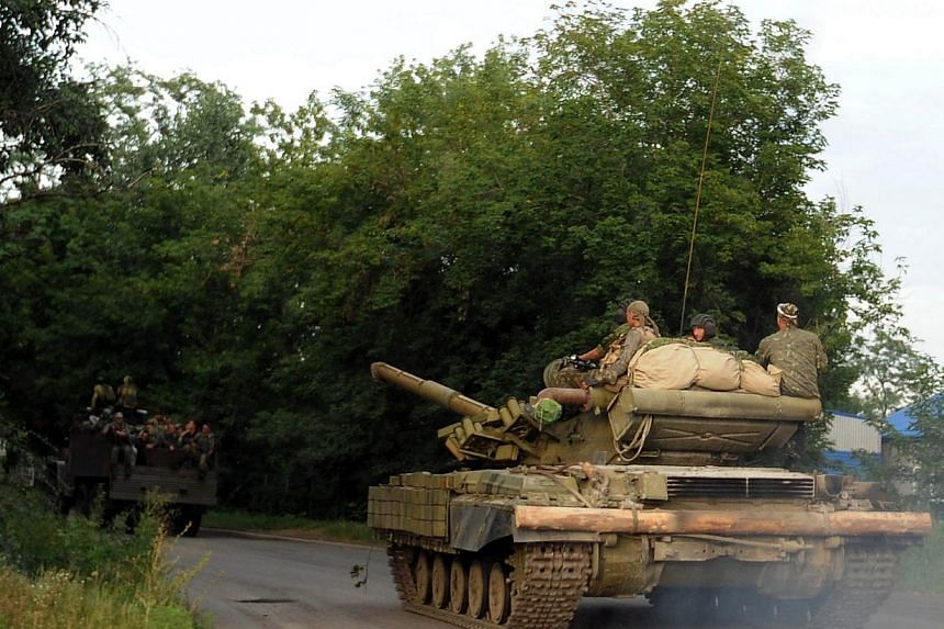 """Pro-Russian separatists ride a tank near Donetsk, eastern Ukraine, on July 19, 2014.A spokesman for Ukraine's Security Council said on Sunday, July 20, 2014, that Russia was continuing to send """"heavy weaponry"""" and other arms to separatists figh"""