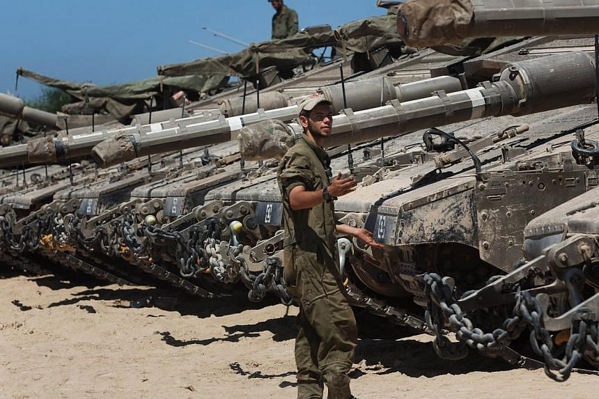 Israeli soldiers work on their Merkava tanks in an army deployment area near Israel's border with the Gaza Strip on July 11, 2014. Israel's army said Sunday it was expanding its ground offensive against the Gaza Strip, as the bloodiest conflict
