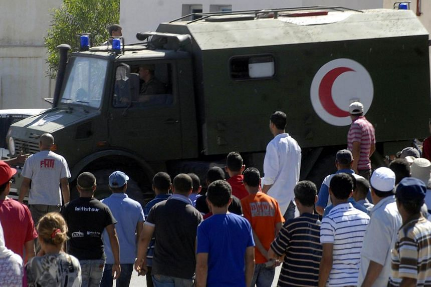 An Army ambulance carrying Tunisian soldiers, injured following an attack near the Algerian border, arrives at a hospital in in Kasserine, located at the foot of Mount Chaambi on July 17, 2014. -- PHOTO: AFP