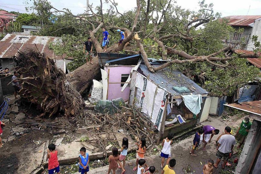 Residents look at a fallen tree which damaged four houses after Typhoon Rammasun battered the town for two days, in Rosario, Cavite city, south of Manila on July 18, 2014. -- PHOTO: REUTERS