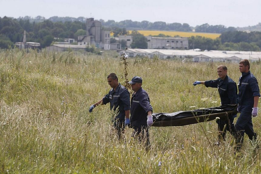 Members of the Ukrainian Emergency Ministry carry a body at the crash site of Malaysia Airlines Flight MH17, near the settlement of Grabovo in the Donetsk region on July 19, 2014. -- PHOTO: REUTERS
