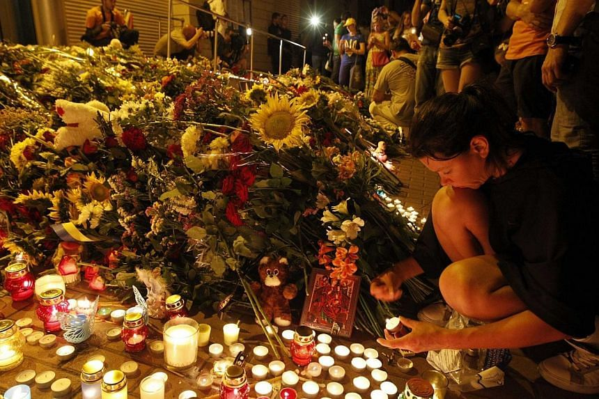 People bring flowers and candles to the Dutch embassy to commemorate the victims of the Malaysia Airlines Boeing 777 plane crash in Kiev, on July 17, 2014.Australians were on Sunday remembering those killed on Malaysia Airlines Flight MH17 at c