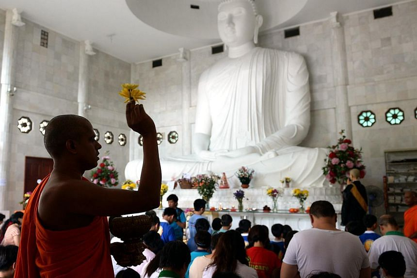 More than a hundred Buddhist devotees and members of the public turned up for a memorial at the Sri Jayanti temple at Jalan Sentul on Sunday morning to mourn those who perished in Malaysia Airlines Flight MH17. -- ST PHOTO: JAMIE KOH