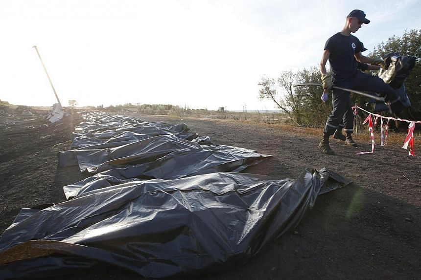 Members of the Ukrainian Emergencies Ministry walk past body bags at the crash site of Malaysia Airlines Flight MH17 near the village of Hrabove, Donetsk region, on July 20, 2014. -- PHOTO: REUTERS