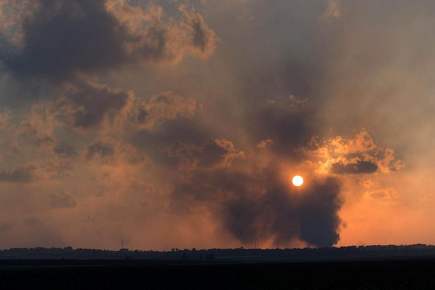 A picture taken on July 20, 2014, from Israel at the southern border with the Gaza strip shows smoke billowing from behind a hill following an Israeli air strike on Gaza City. -- PHOTO: AFP