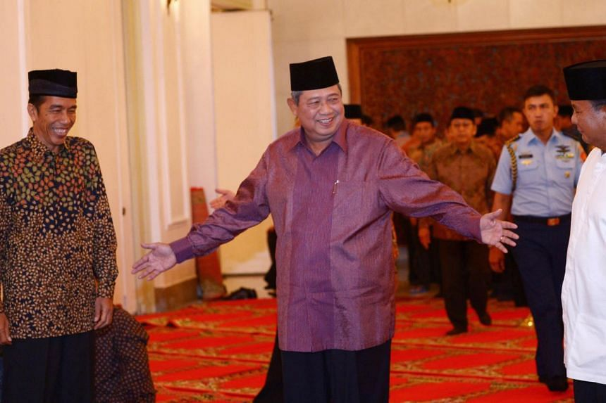 Indonesian president Susilo Bambang Yudhoyono (C) gestures to presidential candidates Joko Widodo (L) and Prabowo Subianto (R) prior to a breaking of fast at the presidential palace in Jakarta on July 20, 2014. Mr Joko is expected to be declare