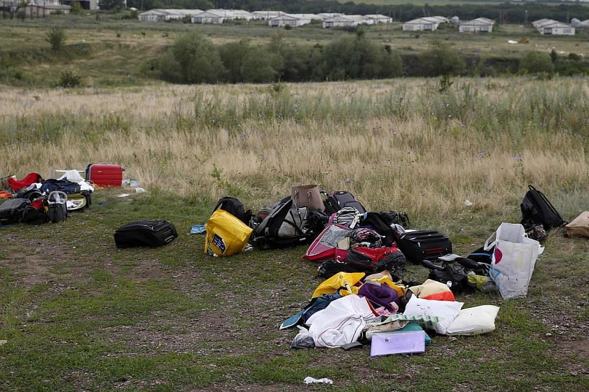 Luggage and belongings are seen near the site of Malaysia Airlines Boeing 777 plane crash, near the settlement of Grabovo in the Donetsk region on July 18, 2014. -- PHOTO: REUTERS