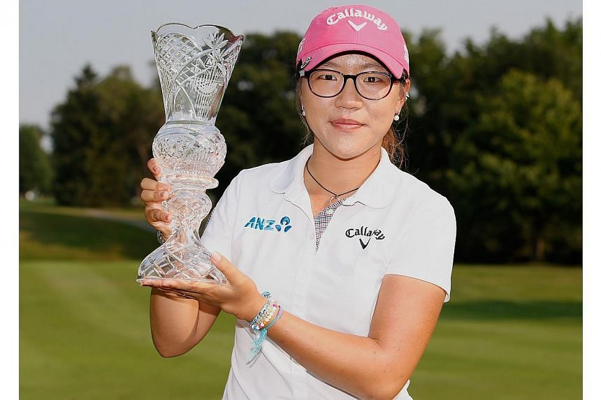 Lydia Ko of New Zealand holds the trophy after winning the the 2014 Marathon Classic presented by Owens Corning and O-I at Highland Meadows Golf Clubin Sylvania, Ohioon July 20, 2014. -- PHOTO: AFP