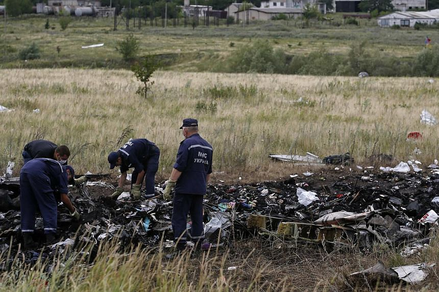 Members of the Ukrainian Emergencies Ministry work at a crash site of Malaysia Airlines Flight MH17, near the village of Hrabove, Donetsk region on July 20, 2014. -- PHOTO: REUTERS