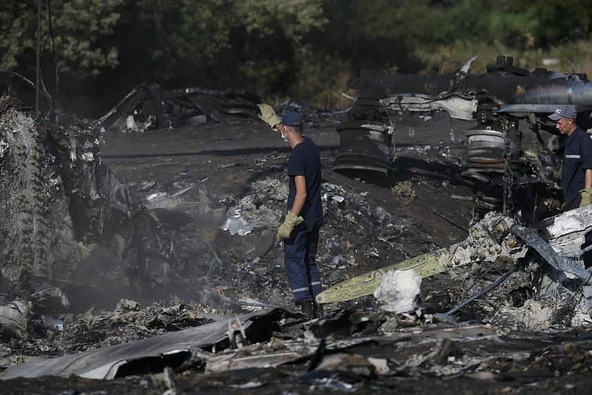 Members of the Ukrainian Emergencies Ministry work at the crash site of Malaysia Airlines Flight MH17 near the village of Hrabove, Donetsk region, on July 20, 2014. -- PHOTO: REUTERS