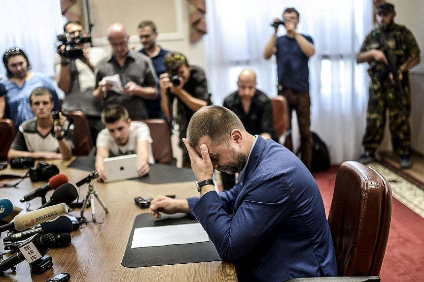 """Self-proclaimed Prime Minister of the pro-Russian separatist """"Donetsk People's Republic"""" Alexander Borodai (centre) gestures as he gives a press-conference in the eastern Ukrainian city of Donetsk, on July 19, 2014.-- PHOTO: AFP"""