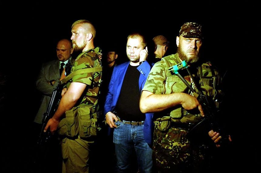 """Self-proclaimed Prime Minister of the pro-Russian separatist """"Donetsk People's Republic"""" Alexander Borodai (centre) stands as he arrives on the site of the crash of a malaysian airliner carrying 298 people from Amsterdam to Kuala Lumpur, near the tow"""