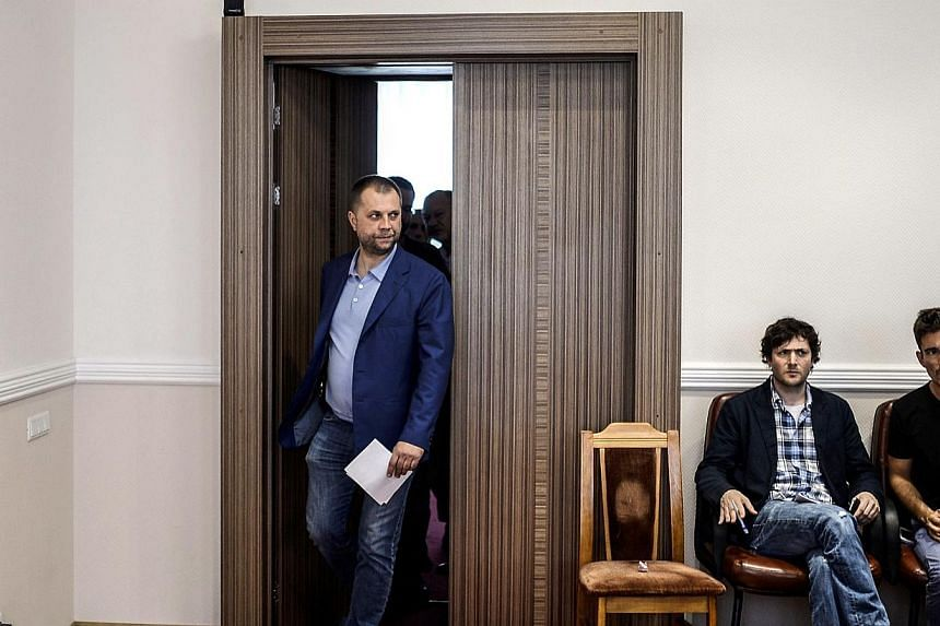 """Self-proclaimed Prime Minister of the pro-Russian separatist """"Donetsk People's Republic"""" Alexander Borodai walks out the door to give a press-conference in the eastern Ukrainian city of Donetsk, on July 19, 2014.-- PHOTO: AFP"""