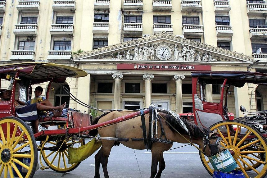 A horse cart is parked in front of the Bank of the Philippine Islands in Manila July 1, 2014.Philippine President Benigno Aquino has signed into law a bill allowing foreign banks to take full control of local lenders, in line with the gov