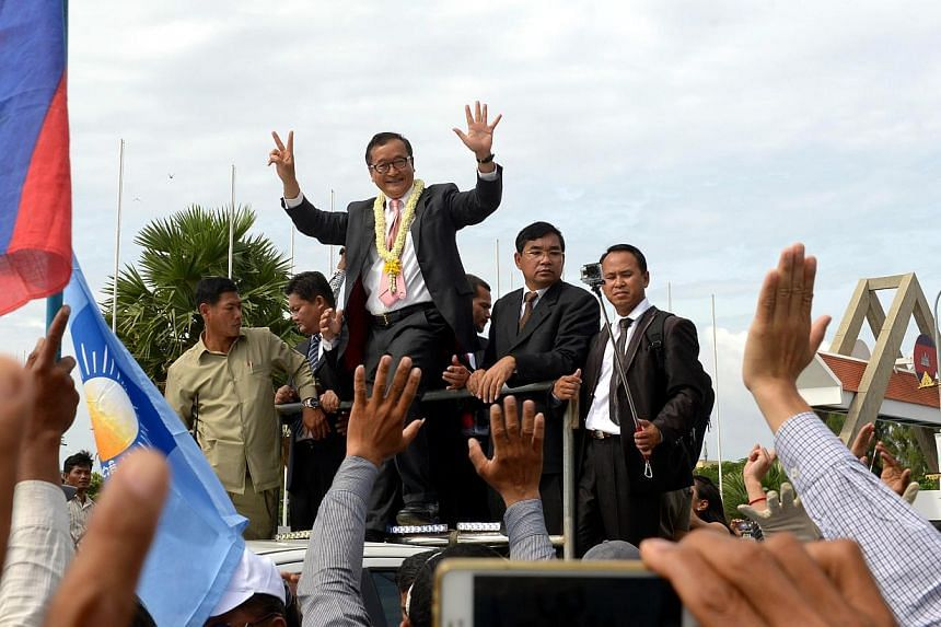 Cambodian opposition leader Sam Rainsy (centre) greets his supporters along a street in Phnom Penh on July 19, 2014.Cambodia's prime minister and the leader of the opposition are set for their first face-to-face talks for nearly a year on Tuesd