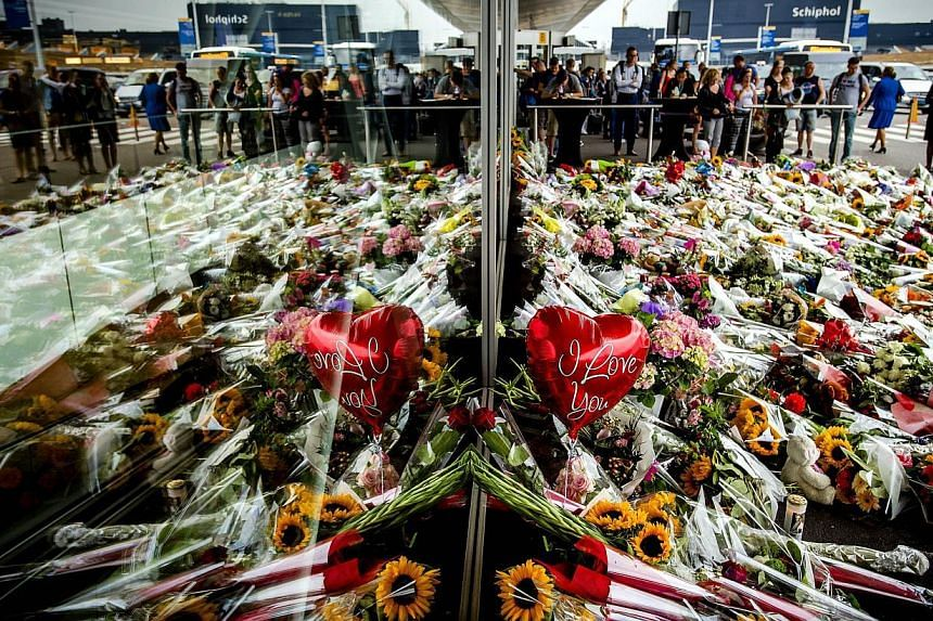 """People look at the flowers left in remembrance for the victims of the MH17 plane crash at Schiphol Airport, near Amsterdam, on July 21.A bereaved Dutch father has written a savagely ironic open letter to whoever shot down flight MH17, """"thanking"""