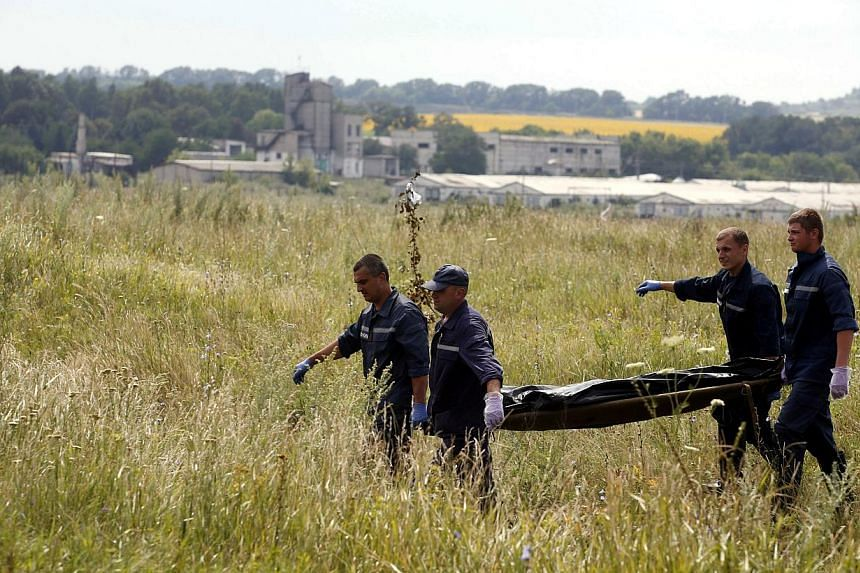 Members of the Ukrainian Emergency Ministry carry a body at the crash site of Malaysia Airlines Flight MH17, near the settlement of Grabovo in the Donetsk region on July 19, 2014.Ukraine is willing to hand over coordination of an investigation