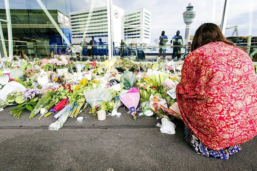 A woman kneels by flowers layed at a remembrance spot at Schiphol Airport, near Amsterdam, on July 20, 2014.The Dutch nation has mourned 193 citizens lost in Malaysia Airlines Flight MH17 disaster in sorrow rather than anger as politicians held